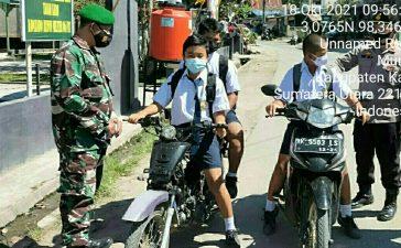 Babinsa Koramil 06/MT Ingatkan Pelajar yang Berangkat ke Sekolah Tetap Gunakan Masker